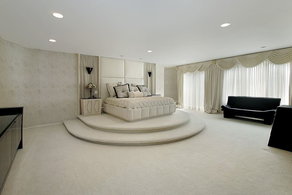 Huge and luxurious master bedroom boasting an elegant bed set along with lovely window curtains and a black set of furniture.