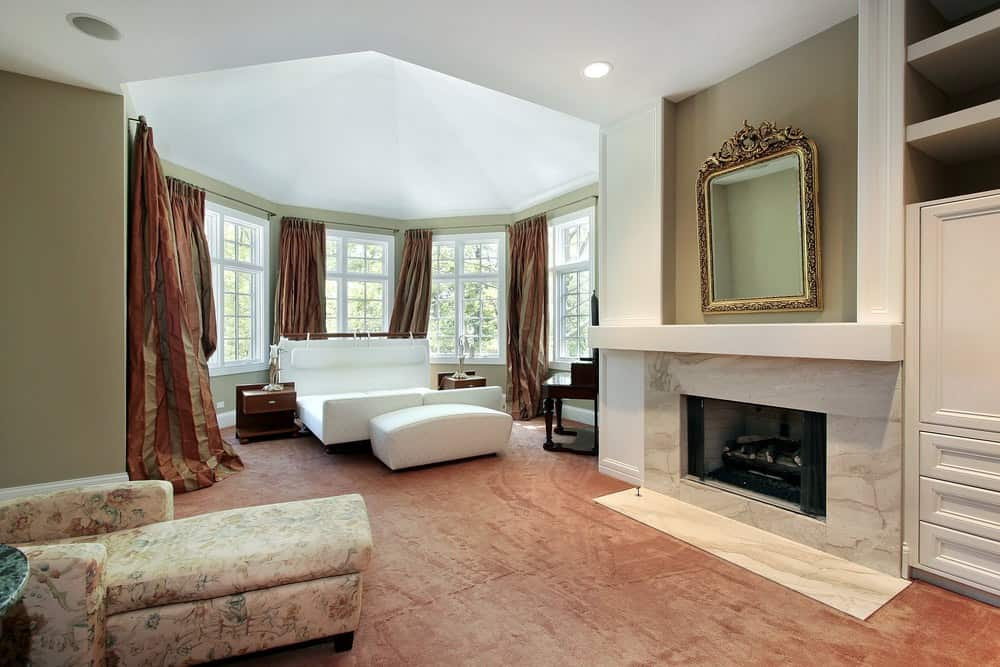 Large bedroom with classy carpet flooring and a large bed set near the windows. The room has a lovely chair in front of the fireplace.