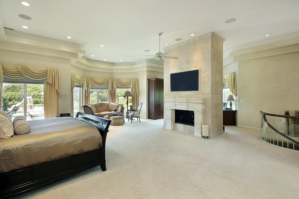 A large master bedroom boasting classy walls and carpeted flooring. The room offers a classy bed and elegant window curtains, along with a fireplace and a TV above it.