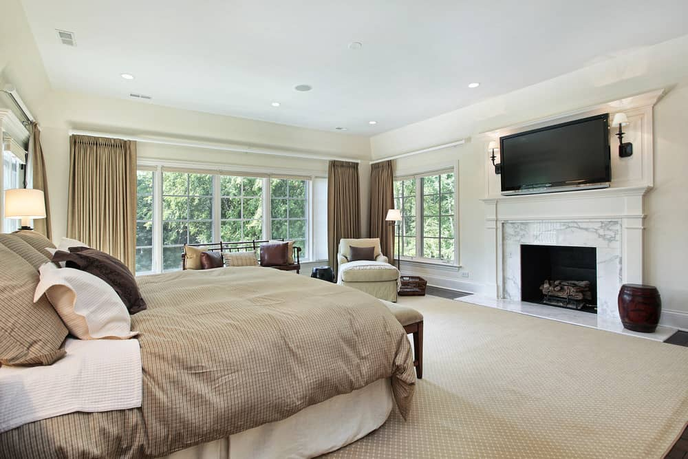 Large master bedroom featuring hardwood flooring topped by a large area rug. The room offers a large bed set along with fireplace and a large TV in front of the bed set.