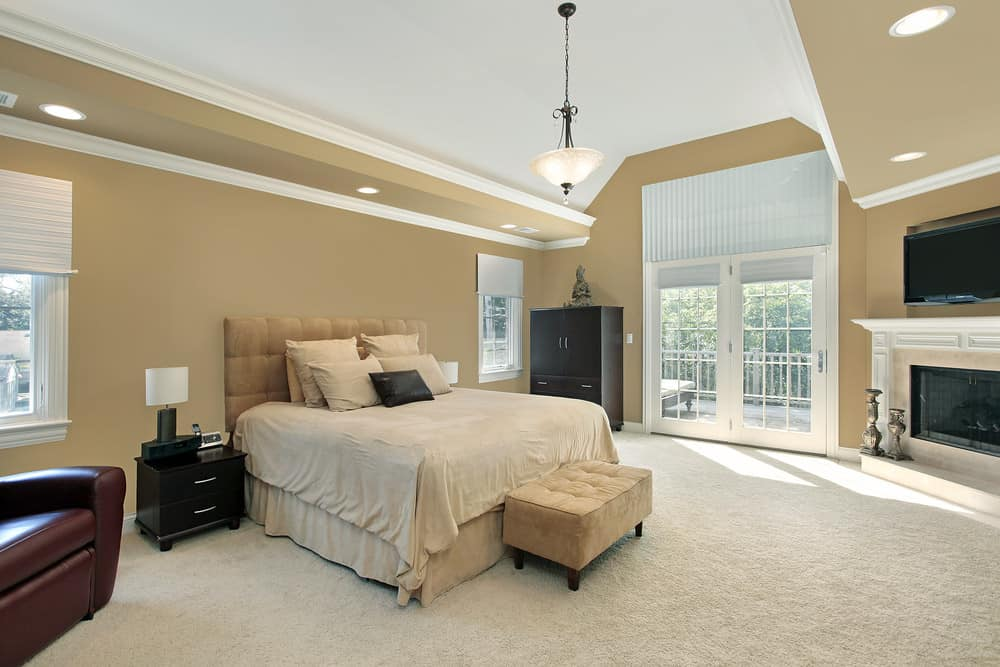 Large master bedroom featuring brown walls and carpeted flooring, along with a beautiful ceiling. The room has a large bed set that looks so elegant along with a fireplace in the corner and a TV on the wall.
