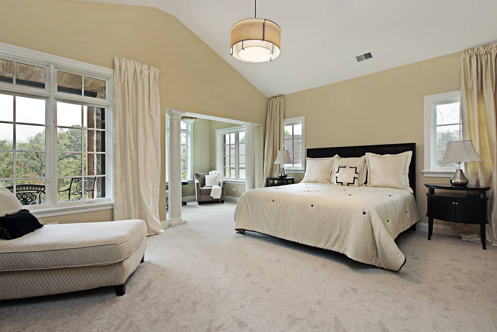 Large master bedroom featuring beige walls and carpeted flooring, along with a large classy bed set with bedside tables on both sides topped by table lamps.