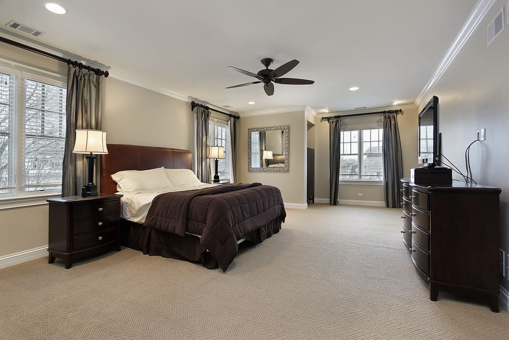 Large master bedroom with light gray walls and carpeted flooring. The room has a large bed set lighted by table lamps on both sides.