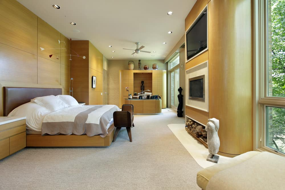 Large modern master bedroom with wooden walls and carpeted flooring. The room has a large bed with a fireplace and a large TV in front. There's also a personal office space on the side of the room.