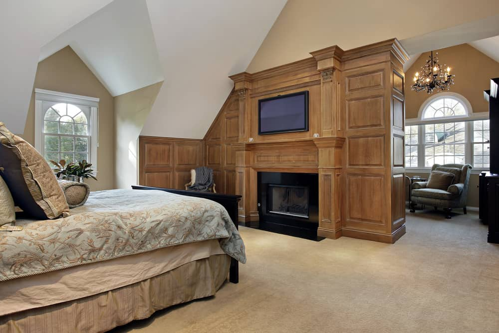 Large master bedroom featuring a large elegant bed set with a fireplace and a TV in front. The room features a tall ceiling and carpeted flooring.