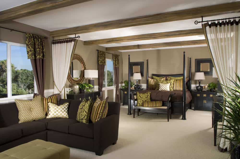 Large master bedroom featuring an elegant bed together with elegant bedside tables topped by table lamps. The room also has a personal living space, featuring an elegant sofa set.