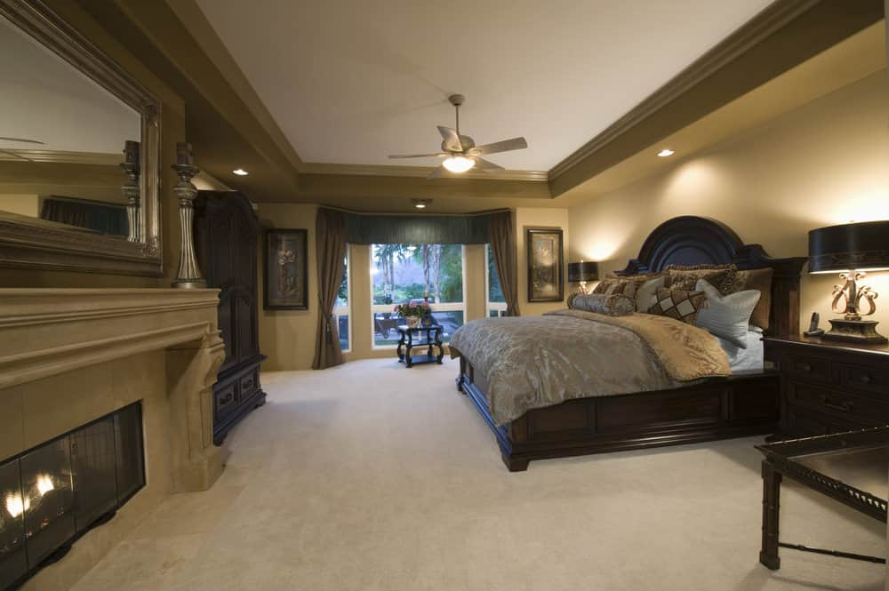 Spacious master bedroom boasting a stunning tray ceiling with brown walls and carpeted flooring. The room has a large bed along with a large fireplace.
