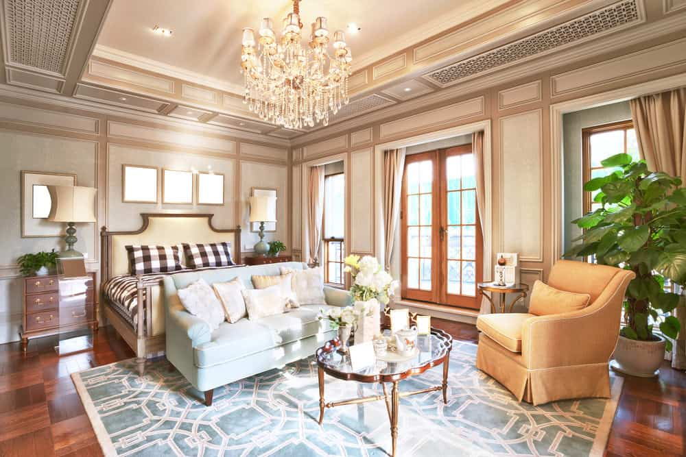 A large and lovely master bedroom lighted by a glamorous chandelier hanging from the gorgeous tray ceiling. The room boasts a classy bed set, decorated walls and hardwood floors topped by a stylish area rug.