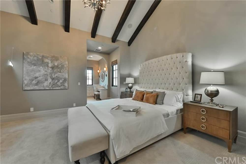 This master bedroom boasts gray walls and carpet flooring. The room offers a large cozy bed set along with its own personal bathroom.