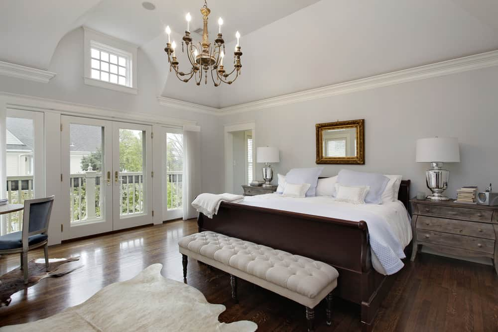 Large master bedroom featuring light gray walls and a tall ceiling, along with hardwood flooring. The room has two rustic bedside tables and a rustic dining nook, lighted by a glamorous chandelier.