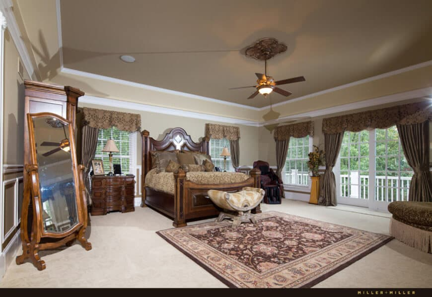 Large master bedroom featuring a gorgeous tray ceiling, carpeted flooring and windows with beautiful brown window curtains. The room offers a large elegant bed set.