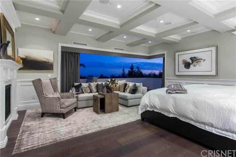 Large master bedroom featuring a coffered ceiling and hardwood flooring, along with a large bed, a personal living space and a fireplace.