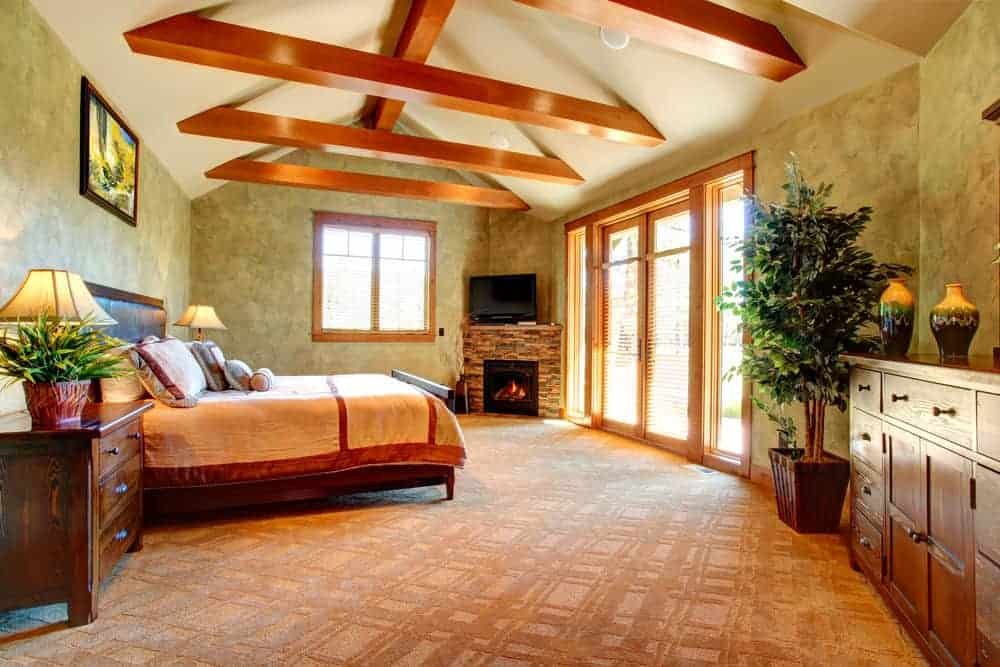 Large master bedroom with brown carpet flooring, green walls and a tall ceiling with exposed beams. The room offers a large bed set and a fireplace in the corner together with a TV on top of it.