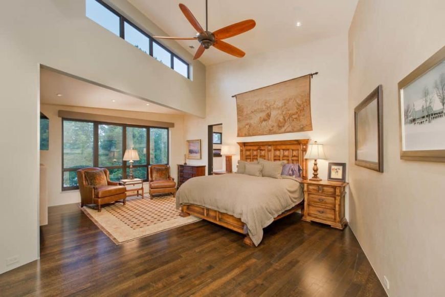 Spacious master bedroom with a tall ceiling and hardwood flooring. The room offers a classy bed set, a sitting area on the side and a personal bathroom.
