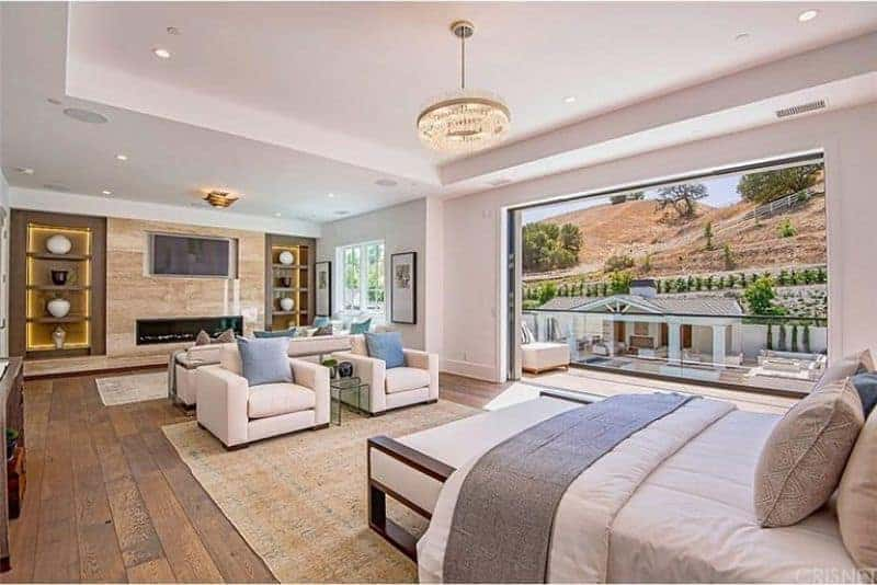 Large master bedroom boasting a comfy bed set and a personal living space with a fireplace and a TV. The room features hardwood flooring and a tray ceiling.