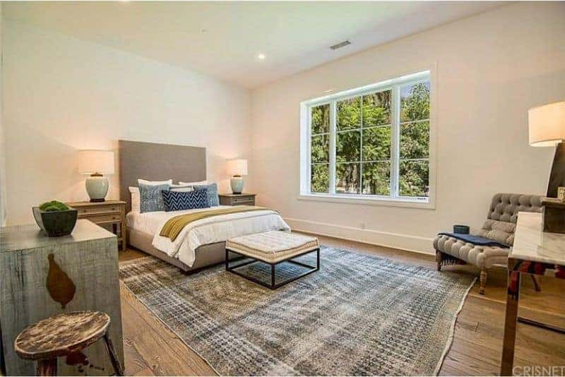 This master bedroom boasts a large modish bed set lighted by table lamps on both sides. The room has hardwood flooring topped by a stylish gray area rug.