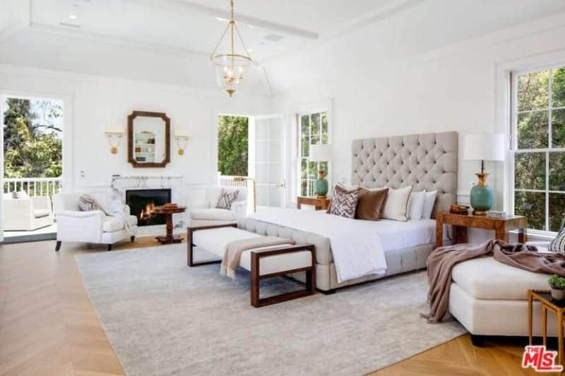 Large master bedroom featuring herringbone-style hardwood flooring and white walls. The room has a large classy bed lighted by beautiful table lamps on both sides. The room also has a sitting area next to the fireplace.