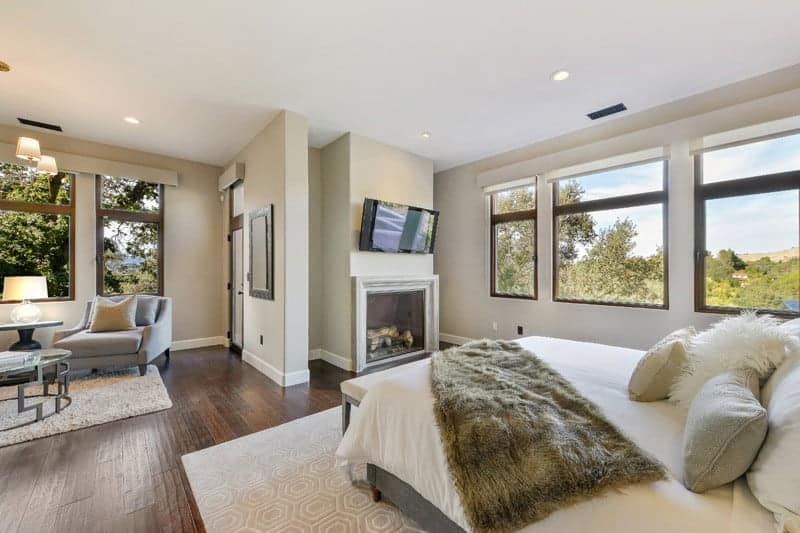 Large master bedroom featuring hardwood floors and beige walls. The room boasts a comfy bed with a fireplace and a TV above it, along with a small living space by the windows.