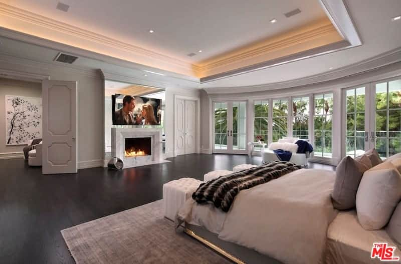 Large master bedroom featuring a stunning tray ceiling and hardwood flooring. The room offers a cozy bed with a fireplace and a large widescreen TV in front. There's a small living space area in the room as well.