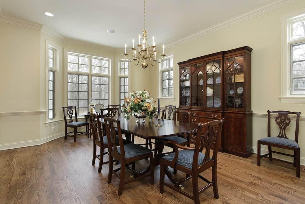 There is a close interaction between the hardwood flooring and dark brown hue of the wooden dining set that matches with the dining room cabinet and the chairs. This is then contrasted by the light beige walls and white ceiling.