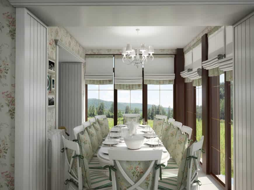 This country-style dining room has white cross-back chairs with light green floral cushions that match with the wallpaper and the shades of the surrounding tall windows that showcase a lush green landscape outside.