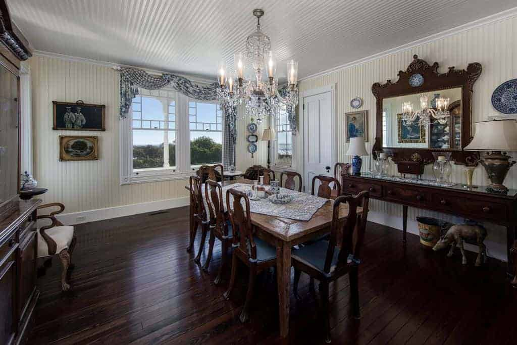 The white ceiling of this country-style dining room matches with the beige walls with the same textured finish. These light hues are contrasted by the dark brown hues of the dining set, the wall-mounted mirror and the hardwood flooring.