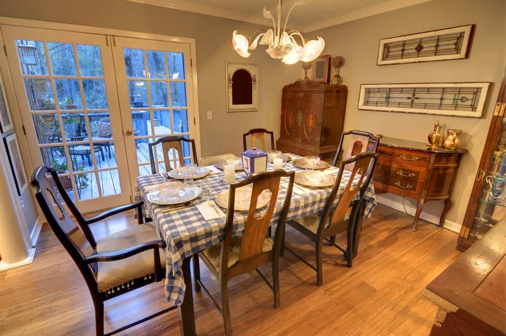 The blue checkered table cloth of this country-style dining room matches with the French glass doors with blue tinted glass. The blue elements are augmented by the warm yellow lights of the lovely chandelier that looks like flowers.