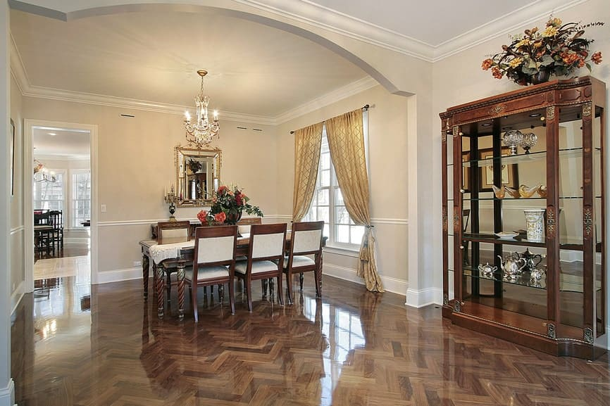The sleek hardwood flooring has a herring bone pattern that brings a complex and shiny background for the elegant dining set with a dark brown hue and beige cushions. This pairs well with the dining room cabinet that is mostly made of glass.