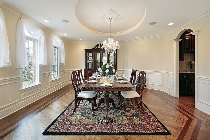The spacious hardwood flooring is mostly covered with a colorful area rug that complements the dark wooden elements of the elegant dining table and its wooden chairs contrasted by the white chandelier from the circular tray of the ceiling.