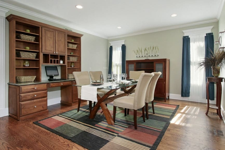 This country-style dining room has a glass-top dining table over a colorful area rug that tops the hardwood flooring. This blends with the table frame and the dining room cabinets that stand out against the light green walls.
