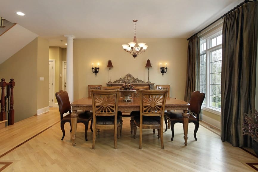 The two dining chairs at each end of the dining table has brown leather cushion while the rest are wooden with a carved back with a sun-like design. This is a complement for the light hardwood flooring as well as the white ceiling that hangs a chandelier over the table.