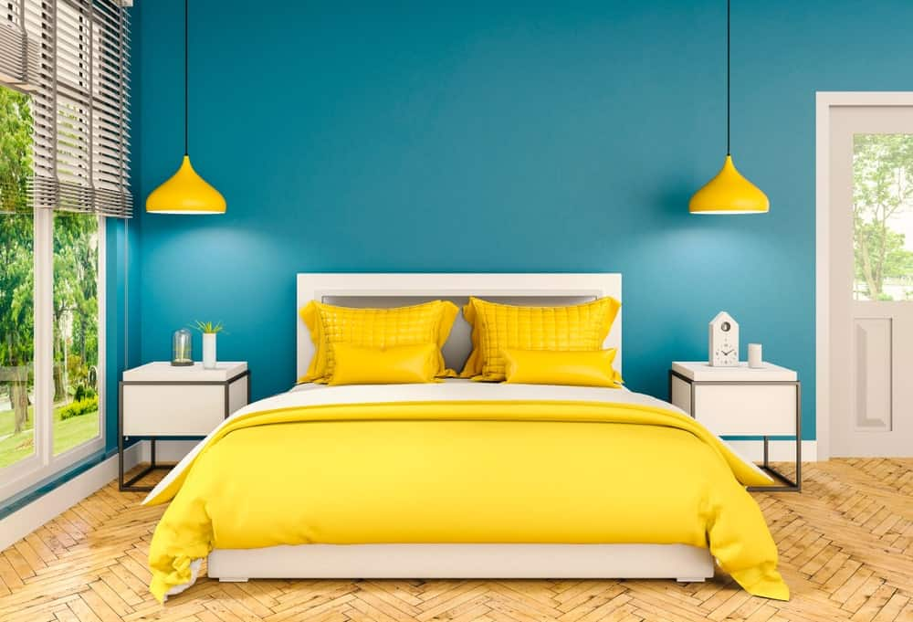 Master bedroom with blue and yellow color scheme showcasing dome pendant lights and a white bed in between sleek nightstands. It has herringbone wood flooring and glass paneled windows covered in roller blinds.