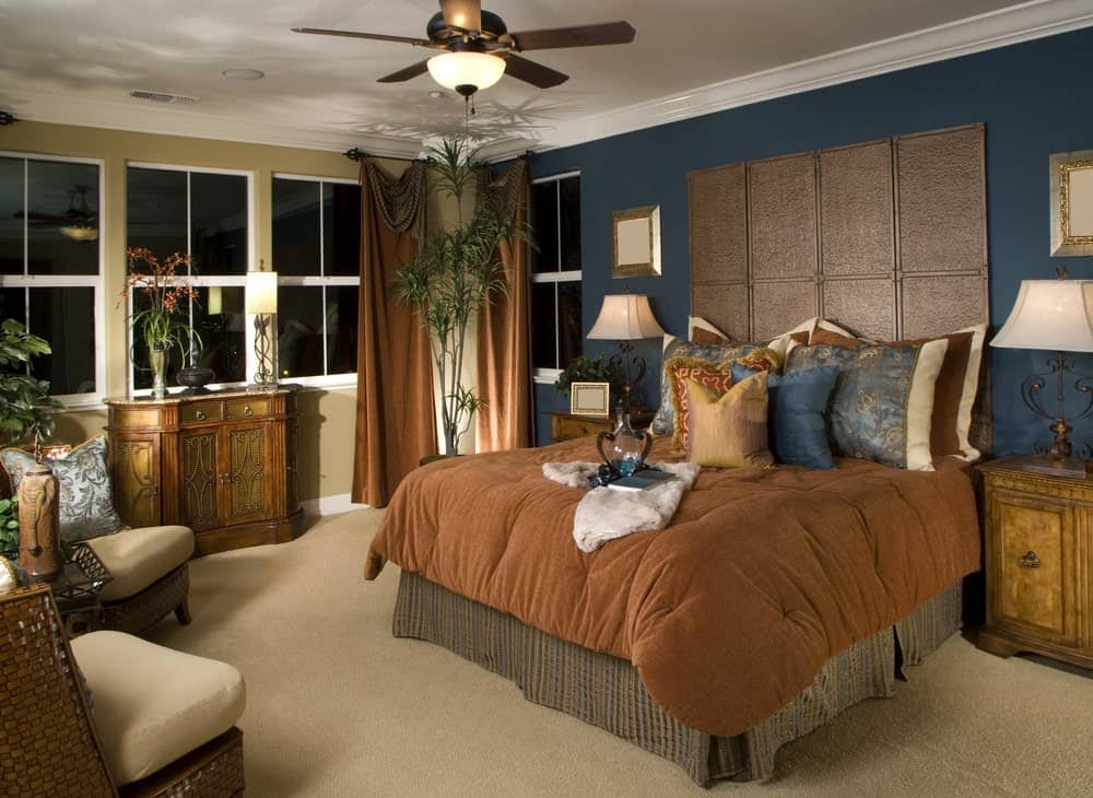 Multi-colored master bedroom with a carved wood console table and a skirted bed placed against the taupe and deep blue walls. It is accompanied by wicker chairs and wooden nightstands topped with ornate table lamps.