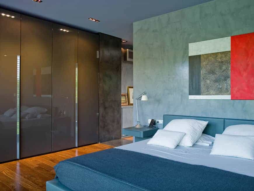 Modern master bedroom with high gloss gray wardrobes and a blue leather bed paired with a built-in nightstand. It is decorated with a sleek artwork mounted on the concrete wall.
