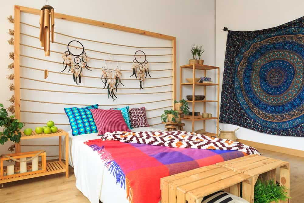 Bohemian style master bedroom designed with gorgeous tapestry and lovely dream catchers that hung above the white bed accented with multi-colored pillows and throw blankets.