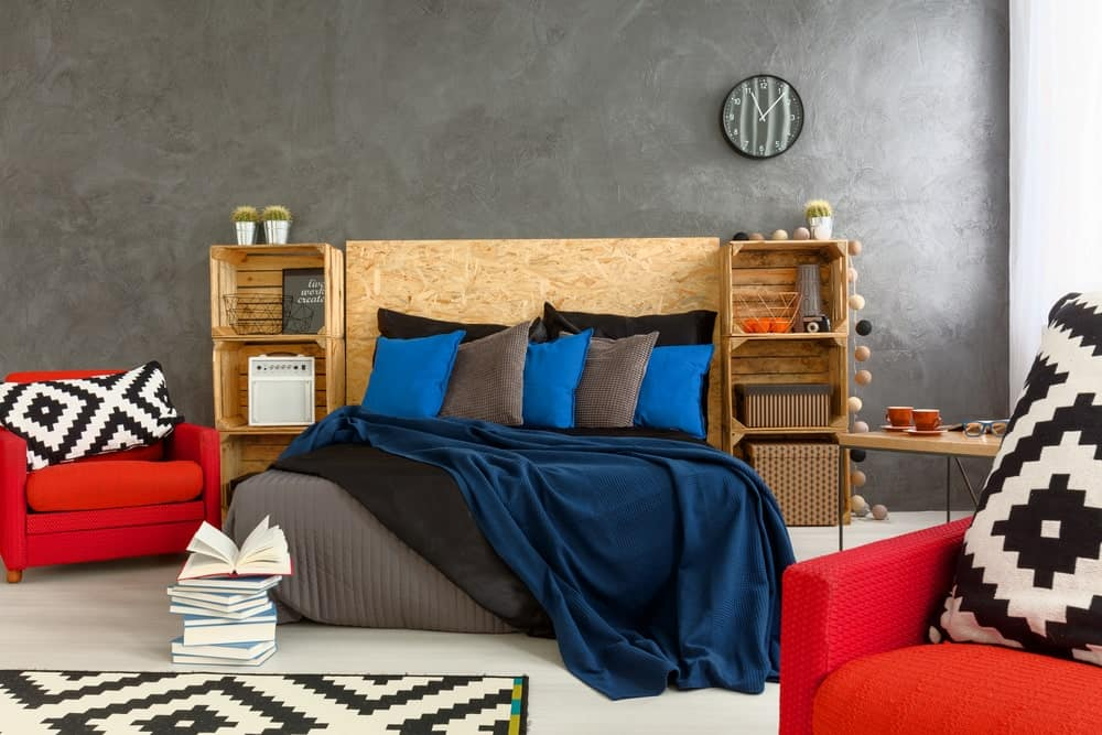 A wooden bed filled with blue and gray pillows complements the shelving units in this master bedroom with red armchairs and a round wall clock mounted on the concrete wall.