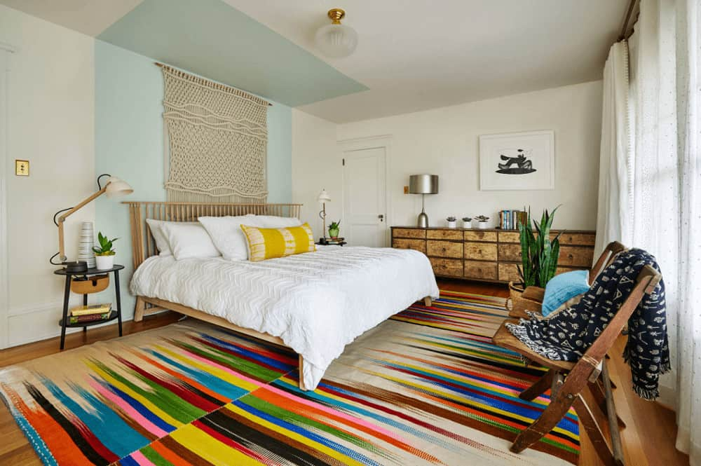 An eye-catching multi-colored rug adds a striking accent in this master bedroom showcasing a wooden bed and long distressed dresser topped with a chrome table lamp.