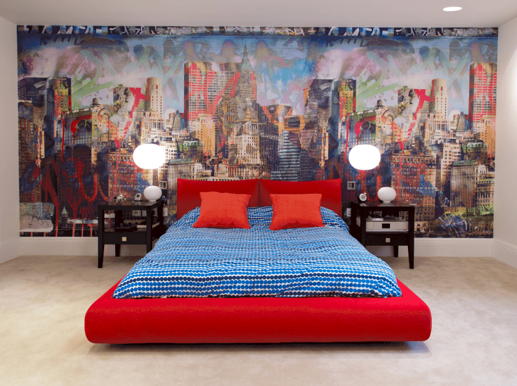 A large scale wall mural is the highlight of this sleek bedroom with dark wood nightstands and a red platform bed dressed in blue dotted bedding.