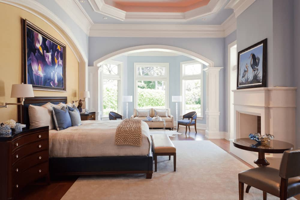This master bedroom offers multiple seating areas and a black bed placed on the arched inset wall. It includes dark wood nightstands and a white fireplace accented with a gorgeous painting.