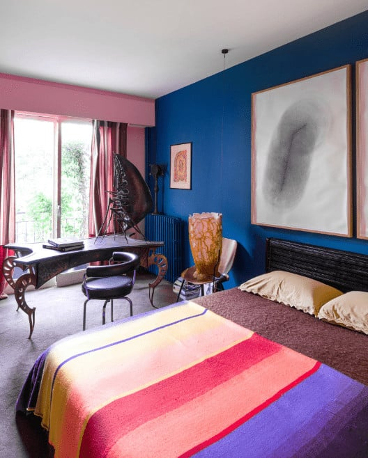 A black round chair sits at an eccentric desk in this eclectic bedroom showcasing carpet flooring and pink and royal blue wall mounted with large artworks.