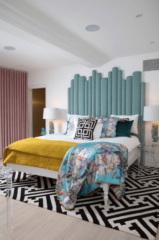 A blue floral throw blanket lays on the stylish bed in this master bedroom with an eye-catching patterned rug and blush pink drapes covering the glazed windows.