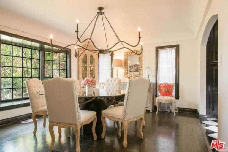The dark hardwood flooring of this Mediterranean-style dining room blends well with the wooden stand of the glass-top round table. This is paired with beige cushioned dining chairs that are brightened by the large French windows and the charming farmhouse-style chandelier.