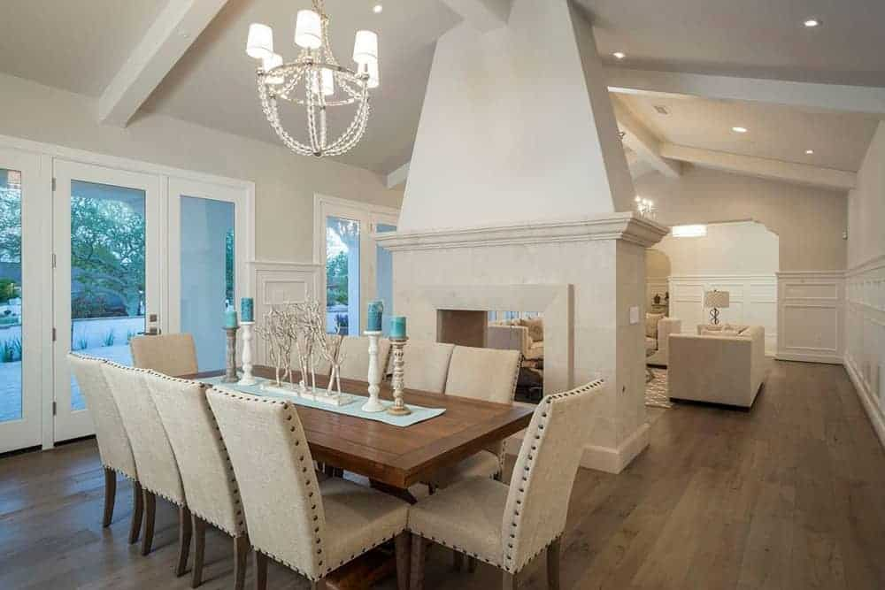These beige cushioned dining chairs have studs on the side of their upholstery. This matches with the hardwood flooring that contrasts the white cathedral ceiling with exposed beams supporting a white modern chandelier.