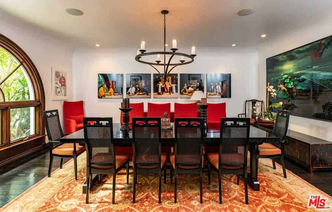 The large black wooden dining table pairs well with the black chandelier and is contrasted by the orange seat cushions of the dining chairs and the patterned area rug. The white wall background is adorned with artworks.
