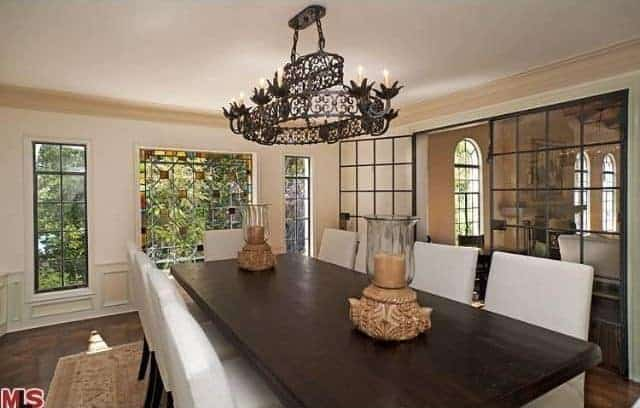 The highlight of this Mediterranean-style dining room is the intricately designed two-tier chandelier that stands out against the white ceiling. This is given a nice background of green trees outside the wide glass windows that brighten up the large dark wooden table.