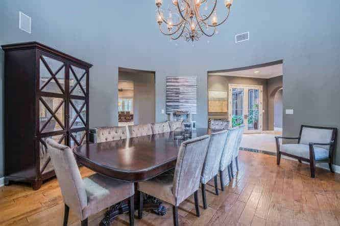 The high ceiling hangs a charming chandelier over the dark wooden dining table. This chandelier stands out against the tall blue walls that are accented with a dining room cabinet filled with glass panels and an abstract painting by the entryway.
