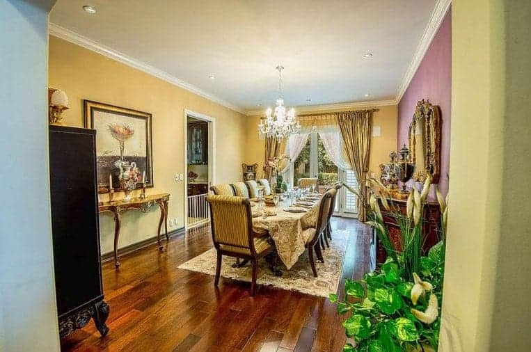 This Mediterranean-style dining room has a dark hardwood flooring that complements the beige tone of the dining set cushions and table cloth that matches with the area rug. This is paired well with the white chandelier that hangs from the white ceiling.