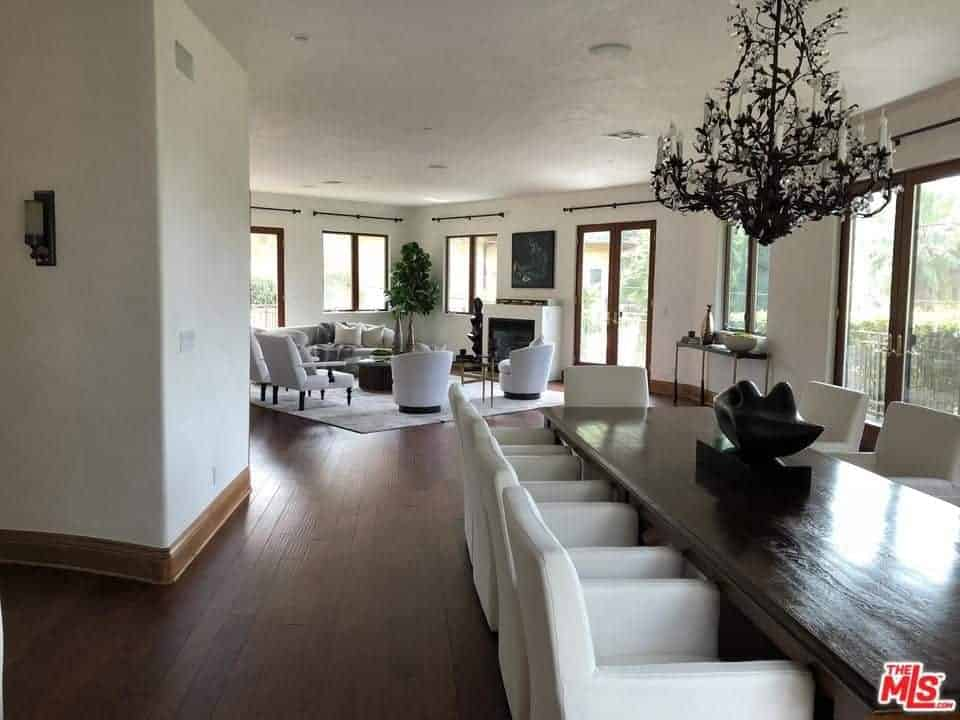 This dining room is illuminated by the glass windows and glass doors of the white walls. This is paired well with the white leather cushions of the chairs that stand out against the dark wooden table and the hardwood flooring.