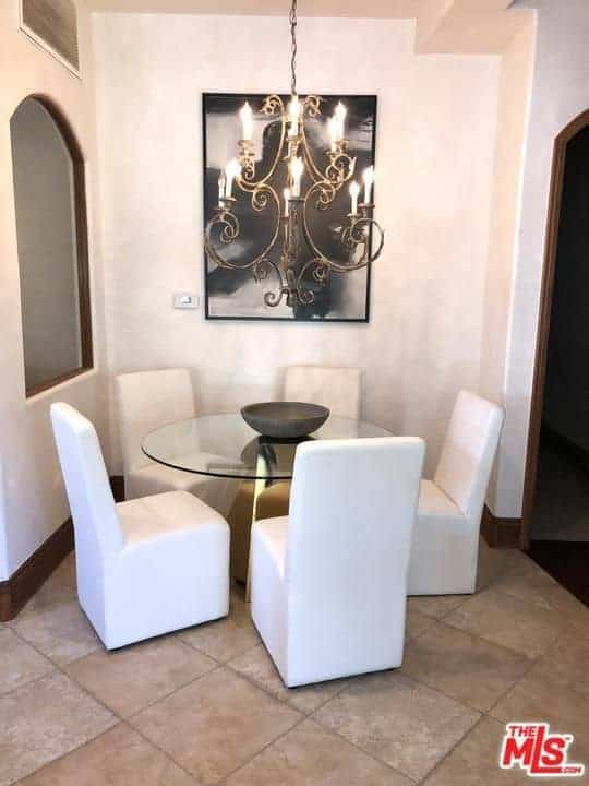 This dining area makes up for its small floor space of beige tiles with some style and elegance. The white upholstery of the dining chairs work well with the white walls that are adorned with a painting and a brass intricate chandelier over the round glass-top table.