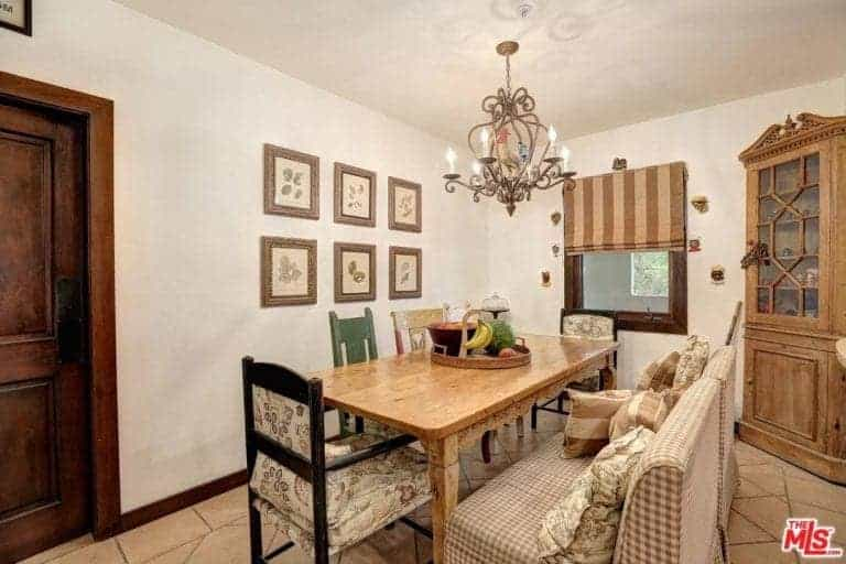 This informal dining room has a comforting demeanor that is brought about by the various patterns on the cushioned bench, various wooden chairs and even the shades of the window. All of these augment the charm of the simple wooden dining table.